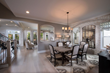 open-concept dining area with light hardwood floors, pendant lighting