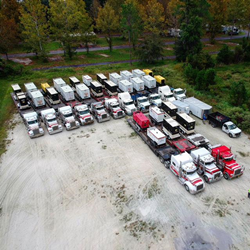 Multiple flatbed trucks loaded with commercial generators staged in a parking lot.