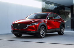 A red 2020 Mazda CX-30 parked near an open concrete building.