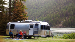 2020 Airstream International Serenity parked by a lake with people sitting outside