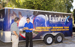 MaintenX team member stands in front of a maintenance truck helping a customer.
