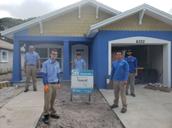 MaintenX team members in blue team shirts stand in front of a blue home that is under construction.