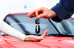a car delivery salesman handing over the car keys and key fob to a new vehicle owner