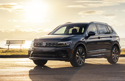 An image of a gray 2020 Volkswagen Tiguan parked next to a lake.
