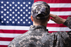 Rear view of a military man saluting the American flag.