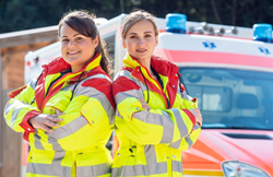 Two women paramedics standing in front of an ambulance