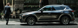 2020 Mazda CX-5 black exterior driver side man in suit walking by the front end