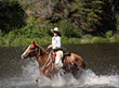 A woman rides a horse through a river in Grand County, CO.