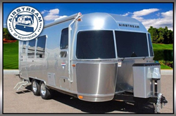 A 2019 Airstream International Serenity 23FB Travel Trailer parked in a grassy area with the Airstream of Scottsdale logo on the upper-left-hand corner.