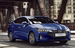 The front and side view of a blue 2020 Hyundai Elantra driving on a bridged road.