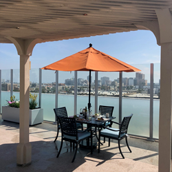 Table with umbrella on roof deck with beach view