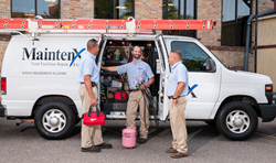 Three MaintenX international HVAC technicians stand in front of their service vehicle.