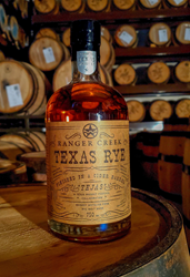 A bottle of the Tejas Ranger Creek Collaboration sitting on a barrel.