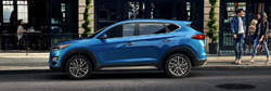 2020 Hyundai Tucson exterior driver side in front of sidewalk with shoppers behind it