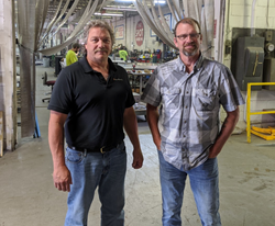 Adam Brown and Rick Rossetti stand on shop floor at their sign company