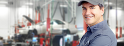 mechanic in auto body shop smiling at camera