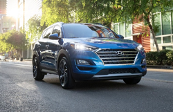 A blue 2021 Hyundai Tucson slowly driving down an urban road.