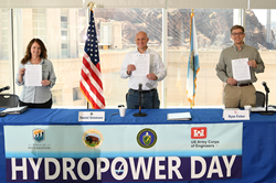 Three people standing at a table holding a piece of paper with Hoover Dam in the background behind them.