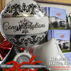 A balloon that says Congratulations on it accompanied by the Area Diesel Service logo