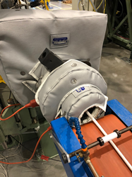 A Shannon thermal reusable, removable insulation blanket covering a plastics extruder.