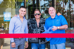 Ribbon cutting ceremony with a red ribbon across the bottom of the picture, about one third of the way up. Three men pose behind the ribbon, all smiling. From left to right is Nick Morgan, the Director of Business Development, Scott Storch, founding partner, and Steve Lobel, founding partner. Steve Lobel is holding a pair of blue scissors, motioning towards the red ribbon. Behind the men is the all glass entrance to the new alcohol and drug rehabilitation center, The Heavenly Center.