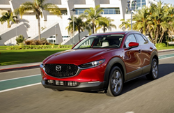 A 2021 Mazda CX-30 driving down a road with palm trees in the background.