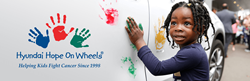 Young girl putting handprint on vehicle next to Hyundai Hope On Wheels logo