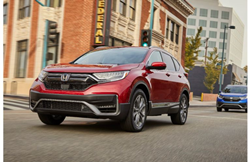 2020 Honda CR-V Hybrid exterior closeup shot of grille and headlights with red paint color in a downtown city area