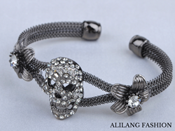 A skull style bracelet in gun metal gray adorned in dozens of glistening rhinestones for the perfect balance of beauty and Halloween darkness.