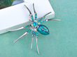 The creepy crawler enriched with light blue rhinestones and painted with glossy enamel.
