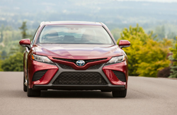 The front image of a red 2020 Toyota Camry Hybrid model parked on the road.