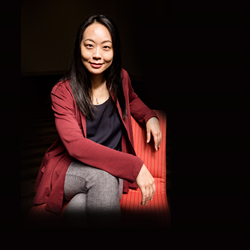 Dr. Peii Chen, sitting on a chair against a black background