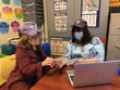 Educator and Speech Language Pathologist conferring with Cap Guard face shield and mask combination