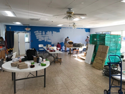 Three volunteers stand in the back of a tiled room, repainting a bright blue wall with fresh white paint. In the foreground, there are stacks of building materials and plastic tables covered in supplies like brown paper towels and  green work gloves.