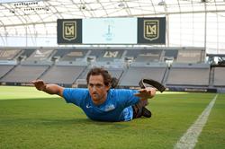 Man on football field exercising