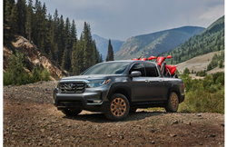 2021 Honda Ridgeline exterior shot with HPD package parked on dirt in a forest mountain clearing with motorbikes in its bed