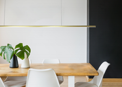 Gold Rae fixture hung over table in tastefully designed living space.