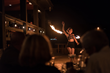 Fire dancer performing infront of guests eating at restaurant.