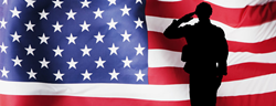 Silhouette of a military member in front of the American flag