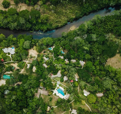 Aerial view of the Chaa Creek resort with river and surrounding rainforest