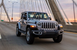 The front and side view of a gray 2021 jeep Wrangler driving on a bridge.