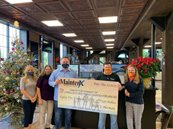 Five people stand together holding a large check from MaintenX International for $85,000, made out to Habitat for Humanity.