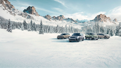Land Rover Boerne Season of Adventure Sales Event exterior shot of model parked on a snowy mountain forest range