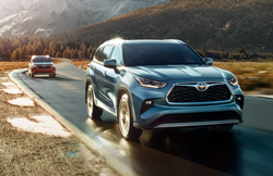 The front and side view of a blue 2021 Toyota Highlander Hybrid driving down a rural road.