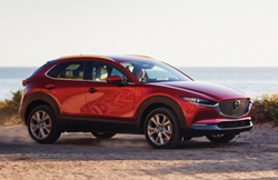 The side view of a red 2021 Mazda CX-30 parked in an open dirt area.