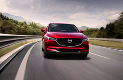 The front side of a red 2021 Mazda CX-5 driving quickly down an open road.