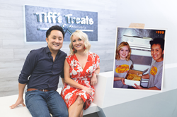 Tiffany and Leon Chen, founders of Tiff's Treats, are pictured in the business' current Austin, Texas headquarters building with an overlapping photo from 1999 showing Tiffany and Leon holding a box of cookies ready for delivery.