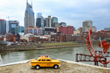 A yellow taxi sits in front of the Nashville skyline.