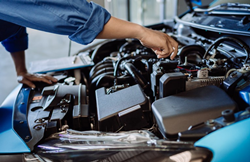 an auto mechanic working on an engine under the hood of a motor vehicle