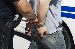 young person wearing handcuffs under arrest